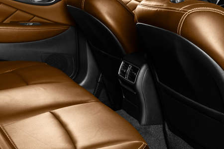 Back passenger brown seats in modern luxury car. Orange perforated leather with white stitching. Car detailing. Leather comfortable brown seats. Car interior details