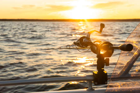 Fishing rod spinning with the line close-up. Fishing rod in rod holder in fishing boat due the fishery day at the sunset. Fishing rod rings. Fishing tackle. Fishing spinning reel.
