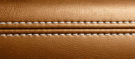Car brown leather interior. Part of perforated leather door handle details. Orange Perforated leather texture background. Texture, artificial leather with stitching. Comfortable perforated leather