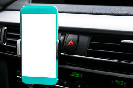 Smartphone in a car use for Navigate or GPS. Driving a car with Smartphone in holder. Mobile phone with isolatede white screen. Blank empty screen. copy space. Empty space for text