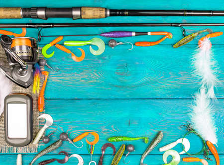 Fishing rod, tackles, reel and fishing baits, reel on wooden board background. Empty space for text