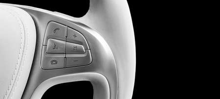 Hands free and media control buttons on the white leather steering wheel, modern car interior buttons on the steering wheel. Black and white