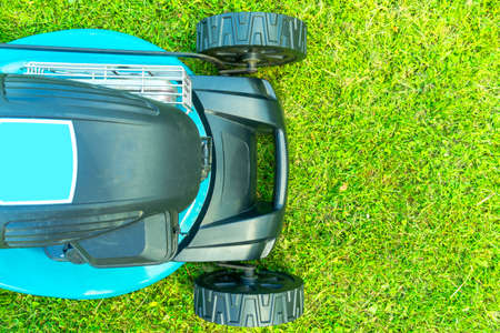 Mowing lawns. Top view lawn mower on green grass. Mower grass equipment. Mowing gardener care work tool close up view. Sunny day. Banco de Imagens