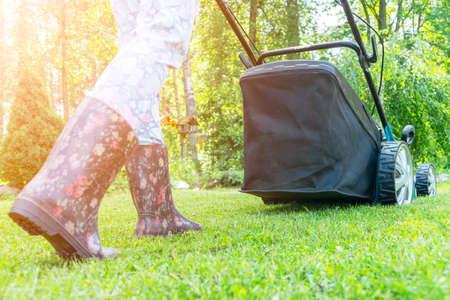 Beautiful girl cuts the lawn. Mowing lawns. Beautiful woman lawn mower on green grass. Mower grass equipment. Mowing gardener care work tool. Close up view. Lawn mowing Banco de Imagens