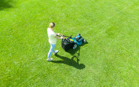 Beautiful girl cuts the lawn. Mowing lawns. Aerial view beautiful woman lawn mower on green grass. Mower grass equipment. Mowing gardener care work tool. Close up view. Aerial lawn mowing Banco de Imagens