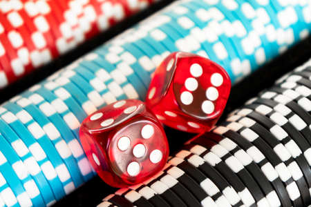 Stack of poker chips with dice rolls isolated background. Poker game concept. Playing a game with dice. Casino Concept for business risk chance good luck. Chips for poker game 免版税图像