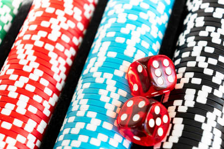 Stack of poker chips with dice rolls isolated background. Poker game concept. Playing a game with dice. Casino Concept for business risk chance good luck. Chips for poker game Stock Photo