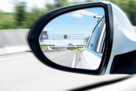 Cars drive along a high road with motion blur background. Car side mirror with traffic. Car rear view mirror with reflection of the traffic