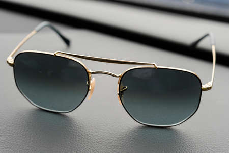Fashionable sunglasses. Sunglasses with mirrored lenses on leather table. Mirrored sunglasses with anti-reflective coating.