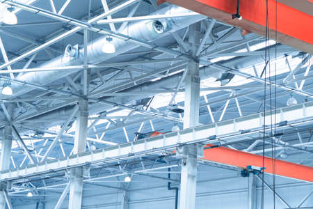 Blue Lights and ventilation system in long line on ceiling of the  industrial building. Exhibition Hall. Ceiling factory construction