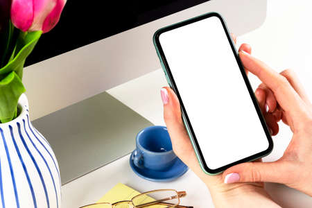 Smartphone mockup in woman hand. New modern black frameless smartphone mock up with blank white screen. Empty space for text. Copy space. Isolated white blank screen.