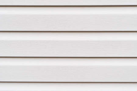 Construction vinyl siding panels pattern. House covered with white plastic vinyl siding. Vinyl siding wall surface with horizontal lines texture background. Wall covered with plastic beige siding. Archivio Fotografico