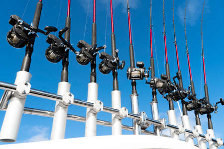 Fishing trolling boat rods in rod holder. Big game fishing. Fishing reels and rods pattern on boat. Sea fishing rods and reels in a row 免版税图像