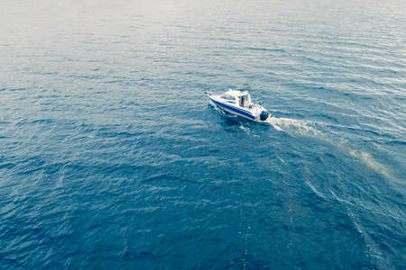 Aerial view fisherman on boat at the ocean. Top view beautiful seascape with the fishing boat. Aerial view fishing motor boat with angler. Ocean sea water wave reflections. Motor boat in the ocean.
