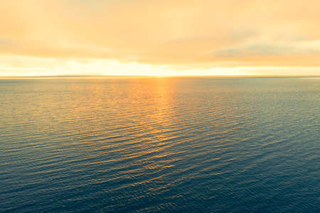 Aerial view of a sunset sky background. Aerial Dramatic gold sunset sky with evening sky clouds over the sea. Sky landscape. Aerial photography.