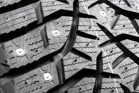 Macro shot winter studded tire. Winter car tires isolated on black background. Tyre protector close up. Square powerful spikes. Black studdable winter tyre profile. Car tires