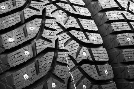 Winter studded tire. Winter car tires background. Tire stack background. Tyre protector close up. Square powerful spikes. Black studdable winter tyre profile. Car tires in a row