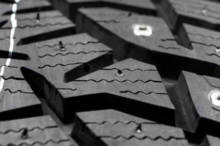 Macro shot winter studded tire. Winter car tires texture. Tyre protector close up. Square powerful spikes. Black studdable winter tyre profile. Car tires Imagens