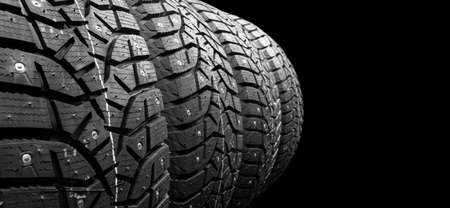 Winter studded tire. Winter car tires isolated on black background. Tire stack background. Tyre protector close up. Square powerful spikes. Black studdable winter tyre profile. Car tires in a row