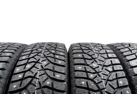 Winter studded tire. Winter car tires isolated on white background. Tire stack background. Tyre protector close up. Square powerful spikes. Black studdable winter tyre profile. Car tires in a row