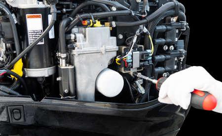 Repairing  outboard marine engine. Motorboat engine seasonal service and maintenance. Mechanic hand performing maintenance on outboard engine Imagens