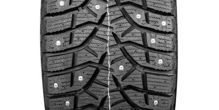 Winter studded tire. Winter car tires isolated on white background. Tire stack background. Tyre protector close up. Square powerful spikes. Black studdable winter tyre profile.