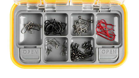 Opened tackle box with fishing hooks and accessories. Fishing hooks in box sections. Case for tackle elements isolated on white background. Fishing accessories background close-up.