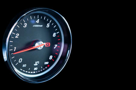 Close up shot of a tachometer in car. Car dashboard. Dashboard details with indication lamps.Car instrument panel. Dashboard with tachometer isolated on black.
