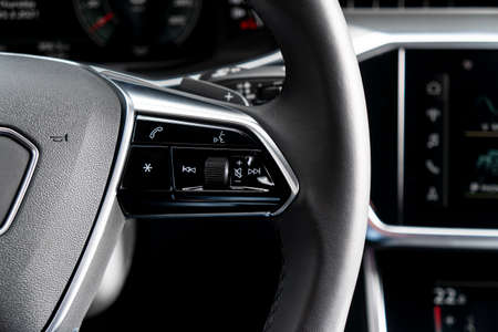 Modern car interior. Steering black perforated leather wheel with media phone control buttons. Car interior details. Car inside