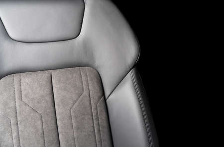 Modern luxury car black leather with alcantara interior. Part of black leather car seat details with white stitching. Interior of prestige car. Perforated leather seats isolated. Perforated leather.