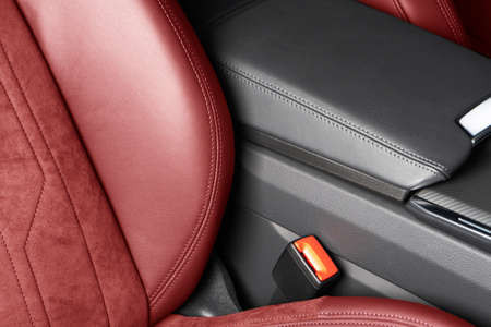 Modern luxury car red leather with alcantara interior. Part of red leather car seat details with white stitching. Interior of prestige car. Perforated leather seats isolated. Perforated leather.