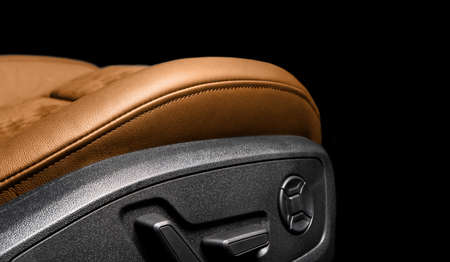 Modern luxury car brown leather and alcantara interior. Part of orange perforated leather car seat details with white stitching. Interior of prestige car. Comfortable perforated leather seats. Stock Photo