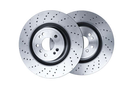 Two car brake disc isolated on white background. Auto spare parts. Perforated brake disc rotor isolated on white. Braking ventilated discs. Quality spare parts for car service or maintenance 写真素材