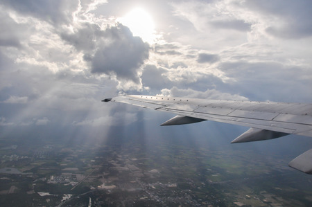 Airplane wing above the clouds from airplane window - Stock Image photo