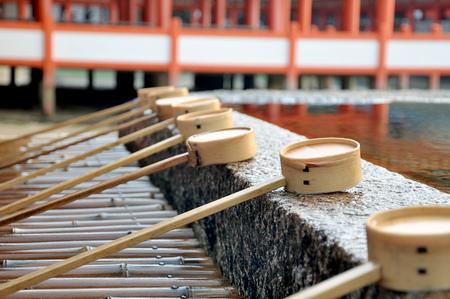 Dipping cups at Itsukushima Shrine  Miyajima Island , japan
