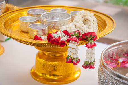 Thai garland Flowers and Water with jasmine and roses corolla in bowl on golden tray  Use for Songkran festival in Thailand