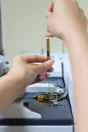 spectrometry: Scientist shooting a sample in the analytical instrument