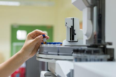 科学者は、琥珀色の薬瓶を保持しています。