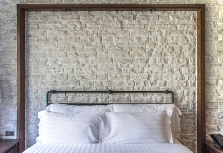 white pillows on a classic bedroom with white brick wall in background photo