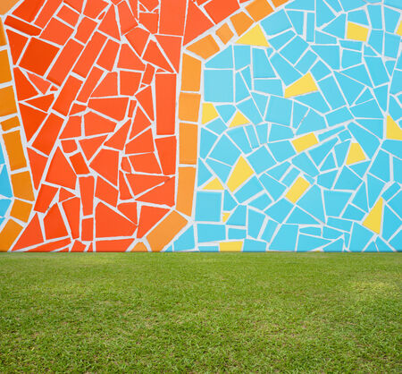 Colorful mosaic tile wall and green lawn Stock Photo