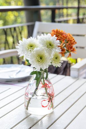 glass vase: Flowers in glass vase on wood table