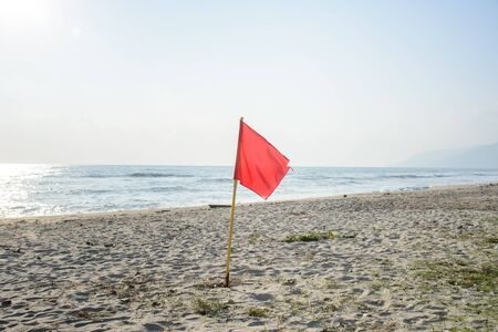 no swimming: Red warning flag on the beach, no swimming
