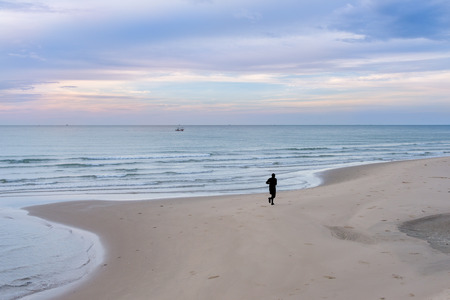 silhouette of man jogging on the beach Stock Photo