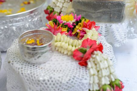 corolla: Thai garland Flowers and Water with jasmine and roses corolla in bowl on golden tray Use for Songkran festival in Thailand