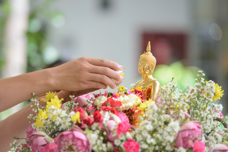 Pouring water over Buddha statue to signify cleansing for the New Year, Songkran festival tradition of thailand