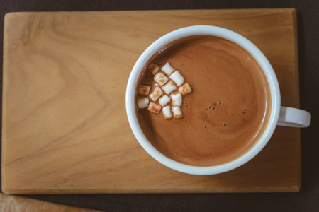 Hot cocoa with mini marshmallows on wooden board