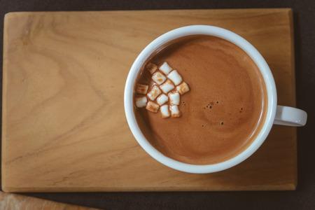 Warme chocolademelk met mini marshmallows op een houten bord