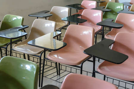 empty classroom: Many lecture chairs arranged neatly in empty classroom.