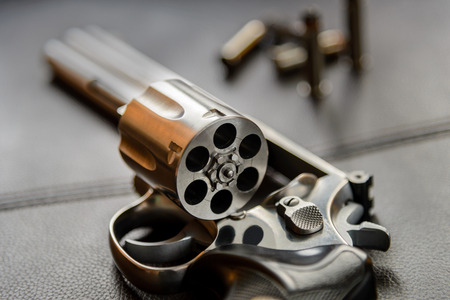caliber: .357 Caliber Revolver Pistol, Revolver open ready to put bullets on leather furniture
