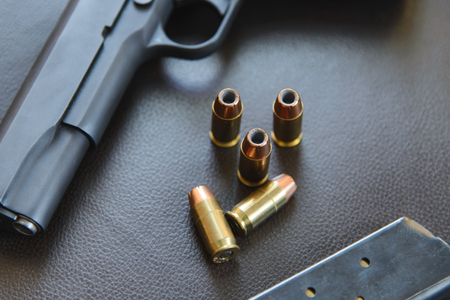 45 caliber: .45 Caliber hollow point bullets near handgun and magazine on leather furniture Stock Photo
